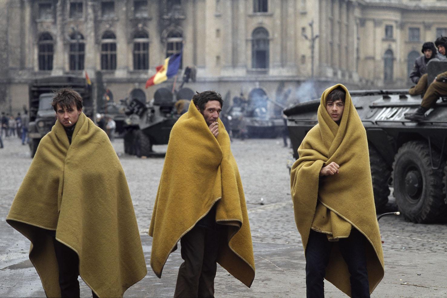Mauro Galligani - Bucarest, Romania, 1989. La fine di Ceausescu. In piazza della Repubblica, tre rivoltosi si riparano dal freddo: è l'alba del 24 dicembre. Nell'aria, l'odore della fine della battaglia, un odore uguale in ogni parte del mondo: polvere, fumo, stanchezza e la paura di non sapere cosa accadrà domani. Il giorno dopo, Nicolae ed Elena Ceausescu vengono arrestati, processati e condannati a morte. Buon Natale, Romania.